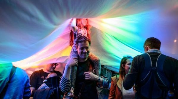 Father with child on his shoulders, with multi-coloured lights