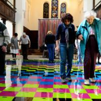 Older visitors travel across brightly lit tile floor