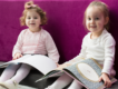 Two children read story books in a cosy corner
