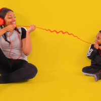 An adult and child sit on floor. They are both wearing large red headphones which are connected by a red curly wire.