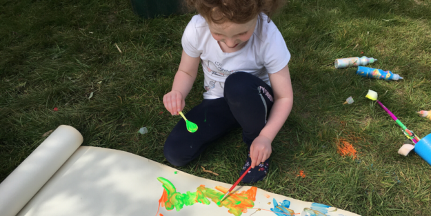 Girl paints on large sheet of paper while sitting on grass