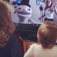 Two small children watch a musician and a puppet on a TV screen