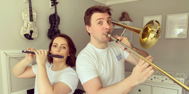 A man and woman pose to camera. She is playing a piccolo, he is playing a trombone.