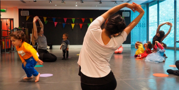 Woman stretches. In the background small children dance below a string of coloured bunting