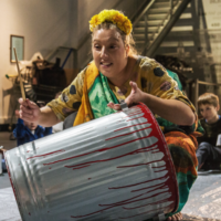 Woman is playing dustbin as a drum. Families sit around in a circle playing smaller drums