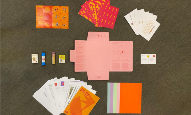 Pack dontents layed out on the floor including postcards, crayons and coloured paper