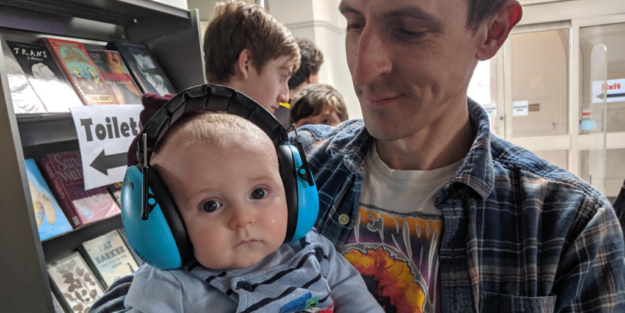Man holding baby who is wearing large blue noise-cancelling headphones