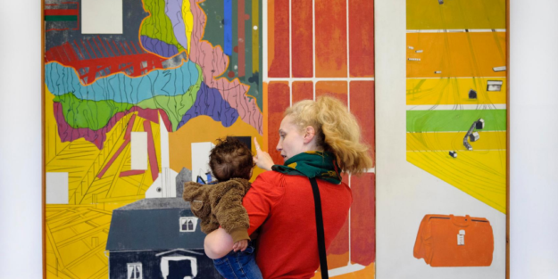 Woman holding baby, looking at large multicoloured artwork on the wall