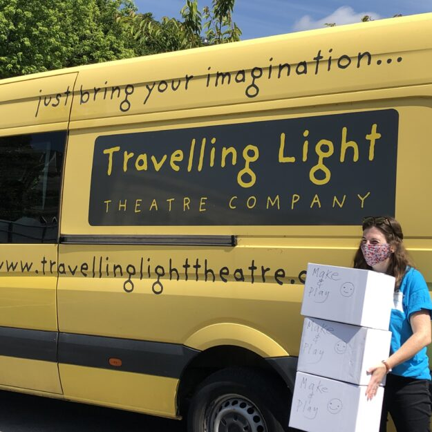 Woman standing in front of Travelling Light van, holding three boxes and wearing a mask