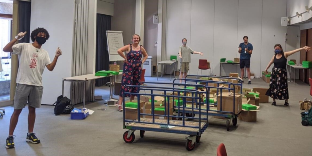 Staff members standing among trolleys and boxes