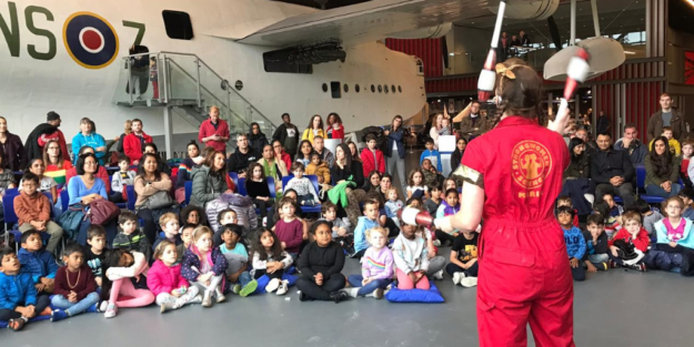 Female juggler wearing red Strong Women Science jumpsuit, in front of crowd of families and an aeroplane