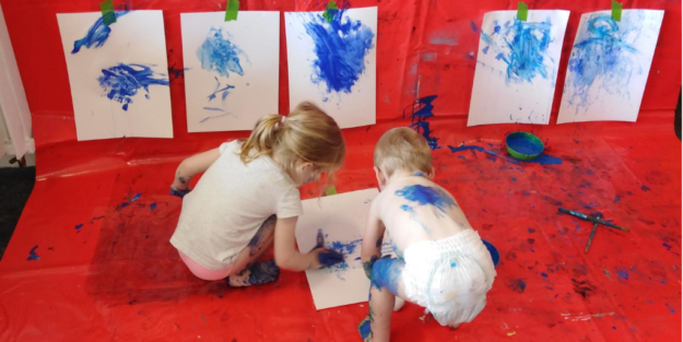 Small girl and boy painting blue on white paper and hanging the sheets in a gallery