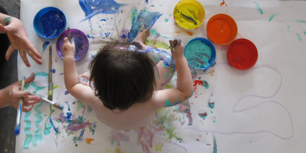 View or small girl's head as she sits on giant piece of white paper, with paint lids of different colours
