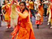 Woman dancing in orange traditional dress, in front of families dancing