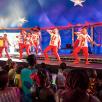 Children sing and dance on stage within a blue and red tent with stars