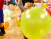Small child grinning on a dance floor full of balloons