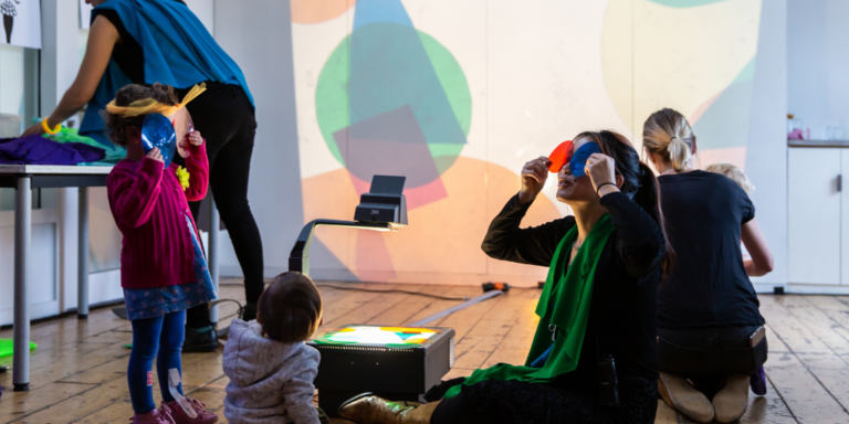 Woman and baby hold coloured plastic over their eyes and project shapes onto the wall