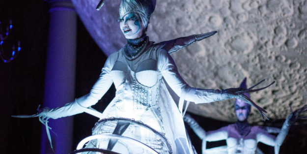 Woman dressed in icy costume in front of giant sculpture of the moon