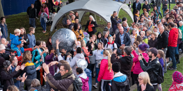 Large group of families stood on grass next to small tent, one is holding a sculpture of the moon