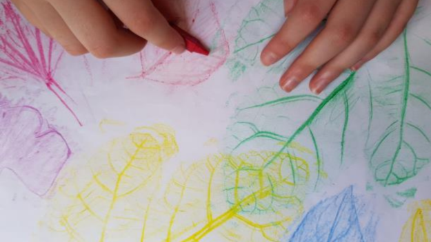 Hand holding a red crayon resting on a print of leaves
