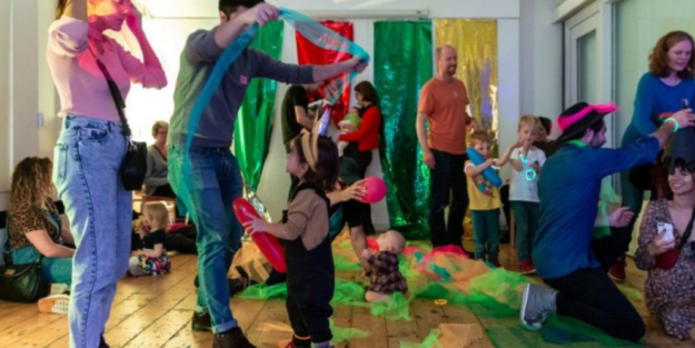 Families playing with long thin strips of coloured mesh and balloons