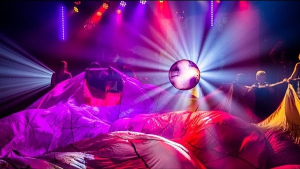 Dark club with coloured lighting - two people hold out a large parachute