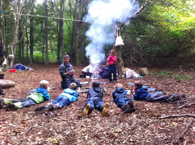 A white man kneels on his knees in the middle of a wooded glade. He has short hair and a navy tracksuit. He is speaking to five young boys who are lying on the ground in front of him. They are wearing outdoor clothing. Behind him is a woman with a small group of children and a young girl standing alongside. There is a campfire in the middle of the gathering.