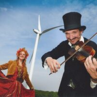 A white man wearing a black suit and top hat is playing a violin on the right side of the picture. Behind him, on the left side of the picture is a woman dressed in a long red dress and a hairpiece. Behind her in the background is a white wind turbine
